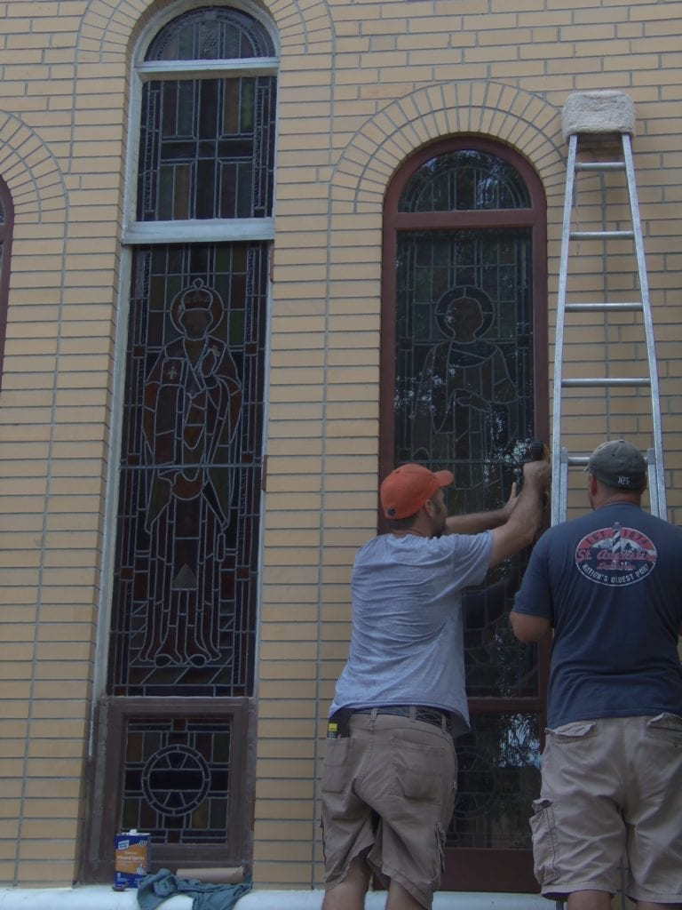 Stained glass church window being installed at a church